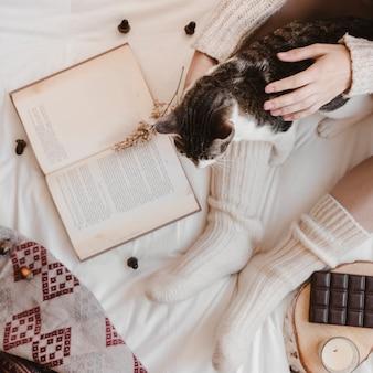 本とチョコレートの近くに猫をペッティングするクリームの女性