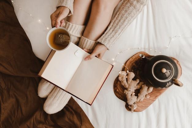 ジンジャーの近くで女性の読書と飲み物