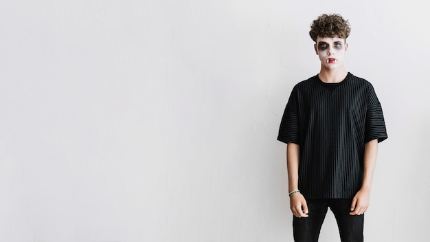 吸血鬼の恐ろしいと牙の黒い服の十代の少年