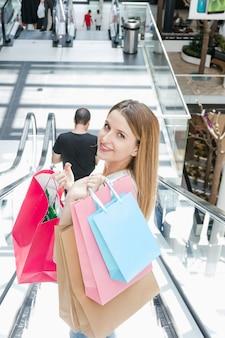 ショッピングモールエスカレーターでショッピングバッグと美しい若い女性