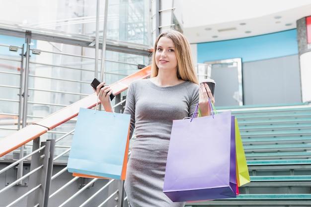 カラフルなショッピングバッグの階段に立っている美しい女性