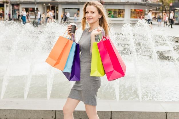 噴水の前を歩くカラフルなショッピングバッグを持つ幸せな女性