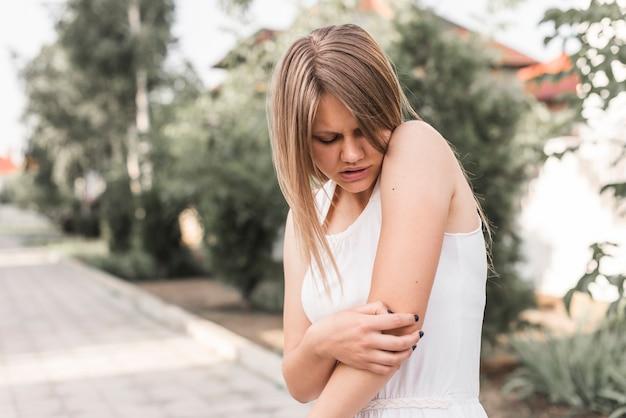肘、痛みを持つ若い女性のクローズアップ