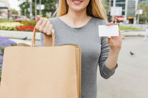 買い物カードと白い白いカードで女性の手のクローズアップ