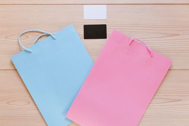 木製の机の上にある空の訪問カードとショッピングバッグの高さのビュー