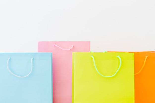 白い表面上のカラフルなショッピングバッグ