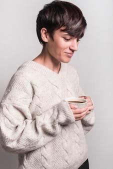 白い背景にコーヒーカップを保持する笑顔の病気の女性の側面図
