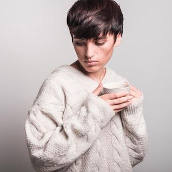 グレーの背景にコーヒーカップを保持するセーターを身に着けているうえの若い女性