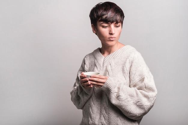 灰色の背景にコーヒーカップを保持しているウールのセーターの若い女性