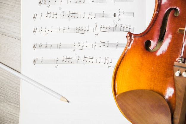 テーブル上の音符の上に鉛筆とバイオリン