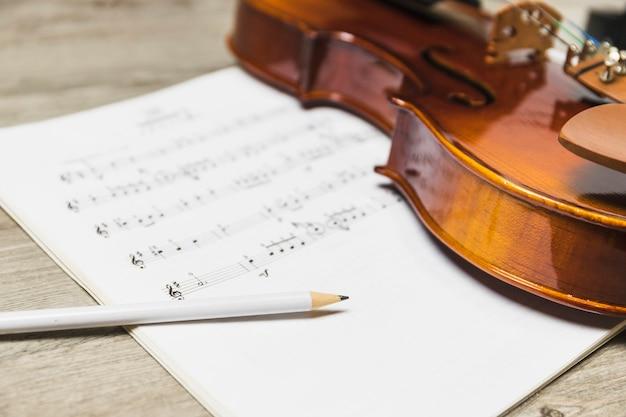 木製の背景の上に音符の上に白い鉛筆とバイオリン