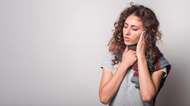 Больная женщина с шерстяным шарфом на шее, страдающим от гриппа