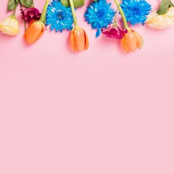 ピンクの背景の上に飾られた花のトップボトム