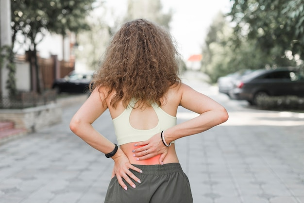 腰痛を持つ通りに立っている女性のリアビュー