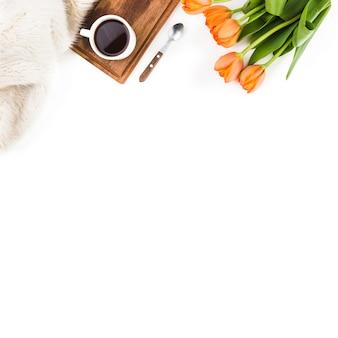 毛皮;スプーン;白い背景にコーヒーカップとオレンジ色のチューリップの花束
