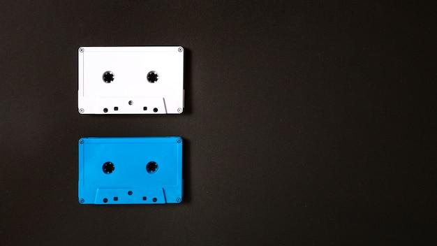 Белая и синяя кассетная лента на черном фоне