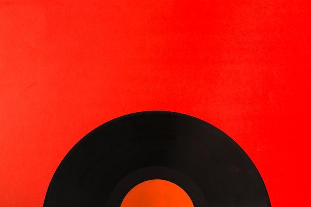 赤い背景の上にビニールレコードのクローズアップ