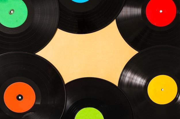 ベージュの背景にカラフルな黒のビニールレコードのオーバーヘッドビュー