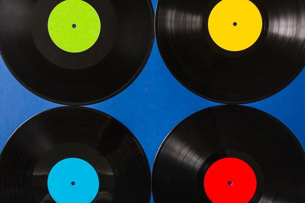 青色の背景にカラフルなビニールのレコードのフルフレーム