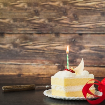 木製のテーブルの上のプレート上のケーキスライスの上に照らされたろうそく