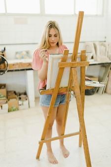 ワークショップでイーゼルに描く若い女性