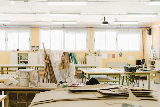 ワークショップのイーゼルで女性の絵画