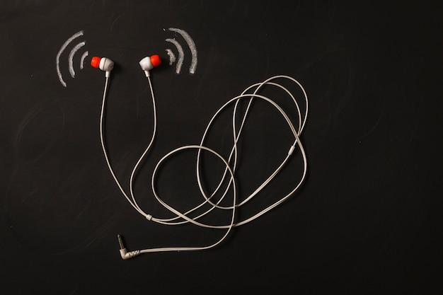黒板のイヤホンの近くの音波のアイコン