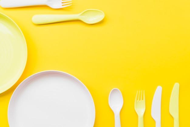 カトラリーのオーバーヘッドビュー;黄色の背景にプレート