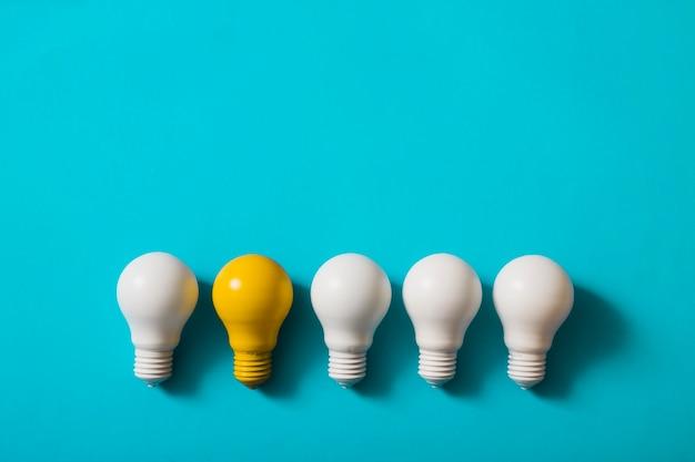 青い背景に黄色の電球と白い電球の行