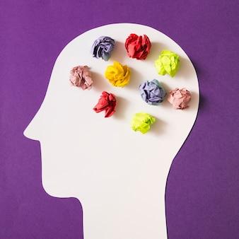 紫色の背景にカットされた白い人間の頭の上にカラフルな朱色の紙