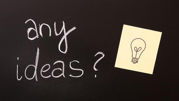 黒板に疑問符と付箋が付いたアイディア