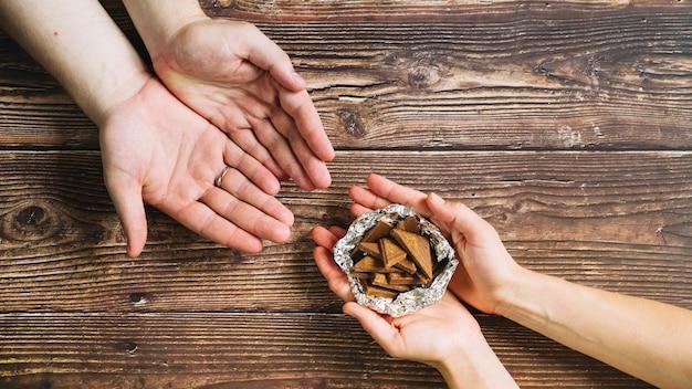 木製の背景にホイルでチョコレート片を与える人