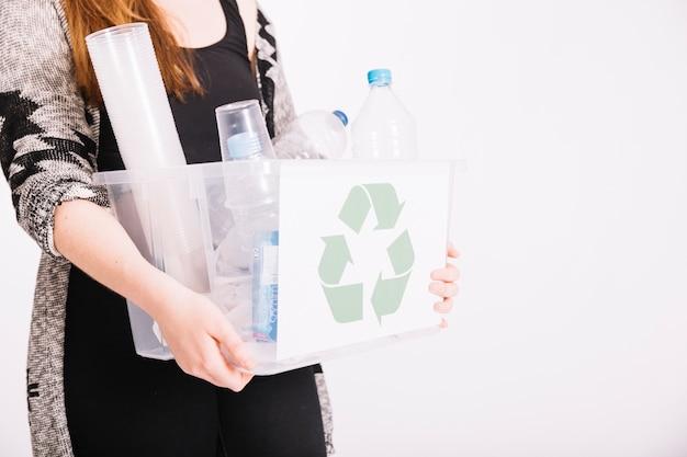 Крупный план женщины, держащей ящик, полный пластиковых предметов для переработки