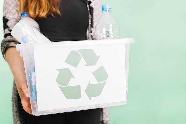 パステルの背景にリサイクルのためにリサイクルクレートを持っている女性