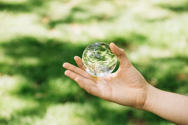 屋外で透明な球を保持している手のクローズアップ