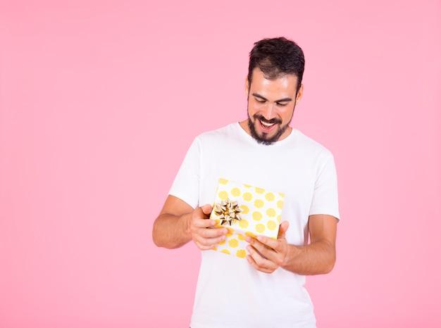 ピンクの背景を手に黄色の水玉のギフトボックスを開いている男
