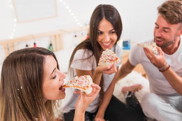 カップルの前でピザを食べる友人のクローズアップ
