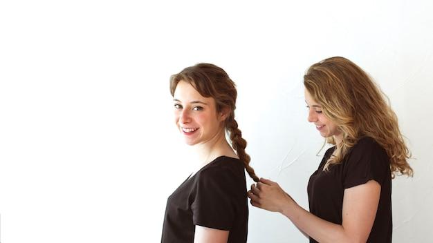 白い背景上に隔離された姉妹の髪を編む笑顔の女性