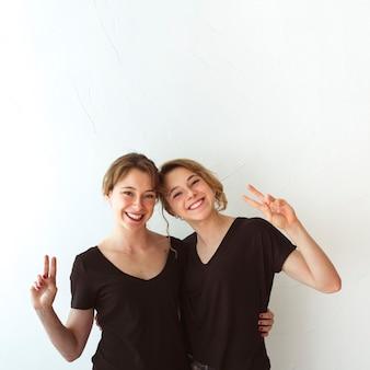 白い背景に勝利を示す若い姉妹笑顔