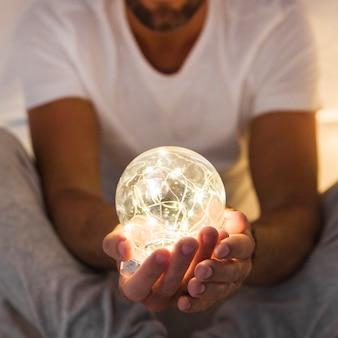 輝く透明な球を保持している男のクローズアップ