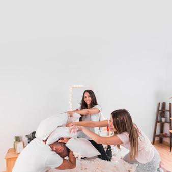 Две женщины, ударяющие человека с подушкой в спальне