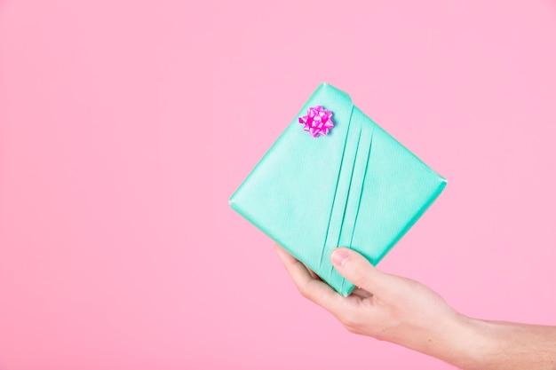 人の手はピンクの背景に包まれたターコイズのプレゼントボックスを保持