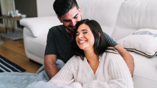ソファの近くでお互いを愛している若いカップルに笑顔