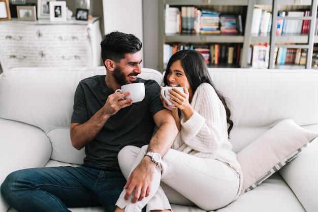 白いコーヒーカップを持つソファに座っている幸せな若いカップル