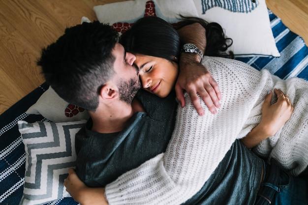 ハードウッドフロアに横たわる額で彼女のガールフレンドにキスする男