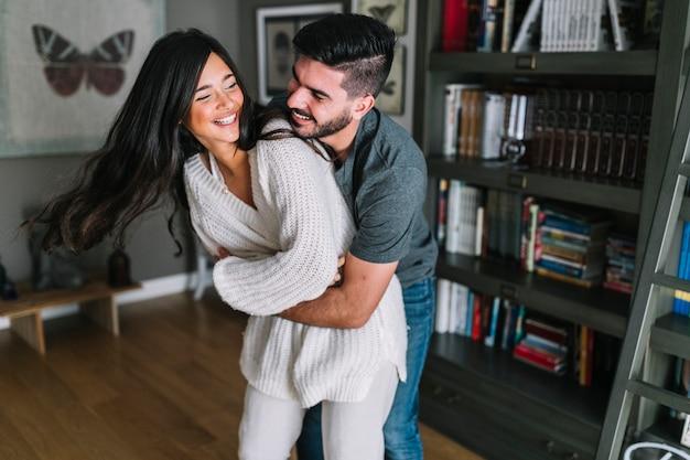 ブックシェルフの前に立っている彼女のガールフレンドを包む笑顔の若い男