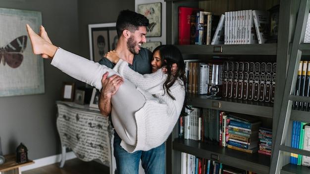 リビングルームで彼女のガールフレンドを運んでいる若い男を笑顔