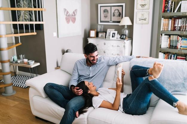 自宅で彼女の本を見せている男の膝の上に眠っている女性