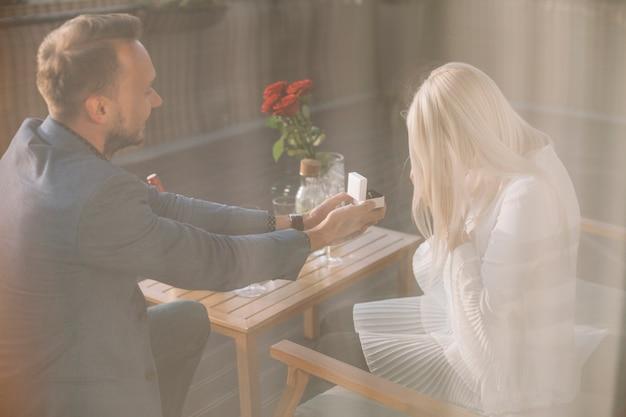 Человек, предлагающий подруге, предлагающий обручальное кольцо в ресторане