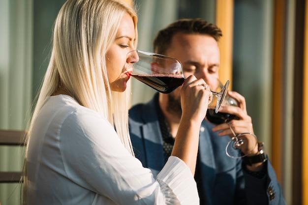 ブロンドの若い女性と彼のボーイフレンドは、赤ワインのガラスを飲む